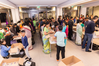 Disciples pack over ten thousand boxes of delicious sweet and savoury prasad