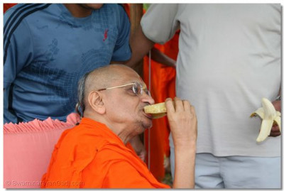 Acharya Swamishree having fruit prasad