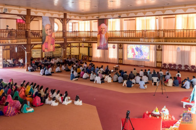 Devotees watch a video darshan of H.D.H Acharya Swamishree's Sneh Sadbhav Parva