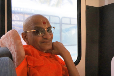 Divine darshan of Acharya Swamishree seated on the shuttle bus
