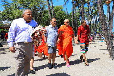 Acharya Swamishree, sants, and disciples walk alongside the beach