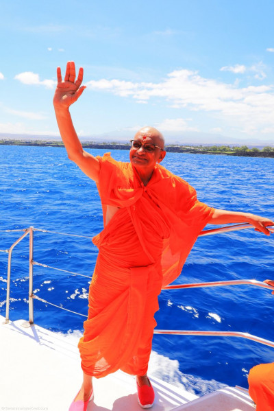 Divine darshan of Acharya Swamishree waving as the boat takes off into the ocean waters