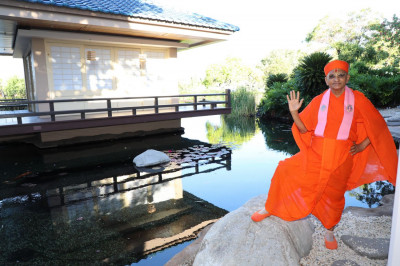 Divine darshan of Acharya Swamishree by a koi pond on the resort