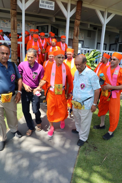Acharya Swamishree is escorted to the helicopter for a ride over the Big Island