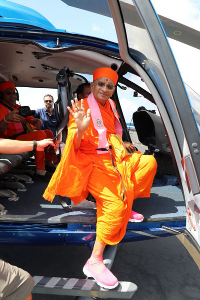 Divine darshan of Acharya Swamishree as He steps into a helicopter for a tour of the Big Island