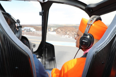 Divine darshan of Acharya Swamishree seated up front with the pilot of the helicopter