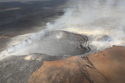 The helicopter flies over an active volcano