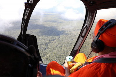 Acharya Swamishree�s helicopter flies over the vast greenery on the interior of the Big Island