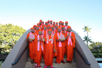 Acharya Swamishree and sants take a group picture on a bridge outside the resort