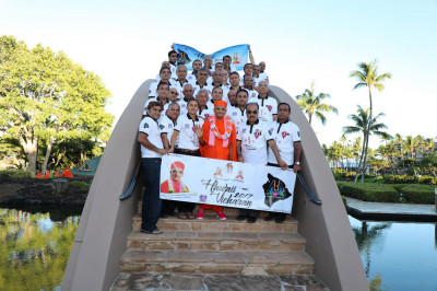 Acharya Swamishree and disciples take a group picture on a bridge outside the resort