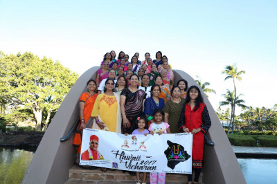 Disciples take a group picture on a bridge outside the resort while holding the vicharan banner