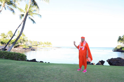 Divine darshan of Acharya Swamishree at a scenic waterside spot on the resort