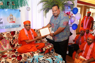 The resort management presents Acharya Swamishree with a special plaque of appreciation