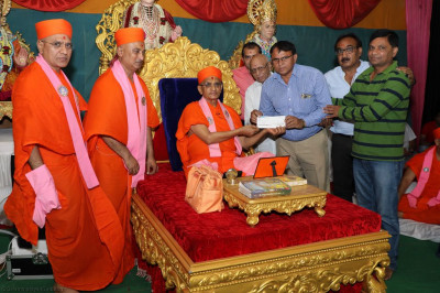 His Divine Holiness Acharya Swamishree presents a donation to a local green charity
