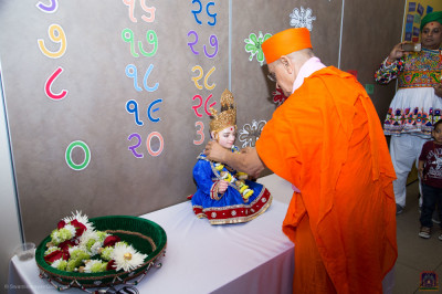 His Divine Holiness Acharya Swamishree Maharaj presents a garland of flowers to Lord Shree Swaminarayan