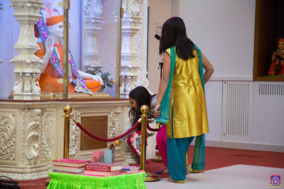 The students present and place their cards at the divine lotus feet of the Lord