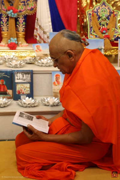 Divine darshan of His Divine Holiness Acharya Swamishree Maharaj at the lotus feet of the Lord with the publication