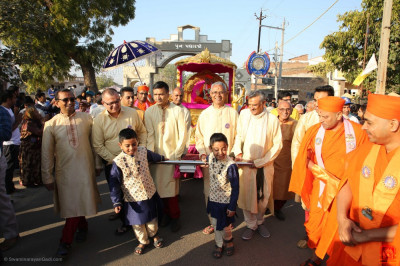 Disciples who have sponsored the scripture recitals pull the golden chariot towards the stage during the morning procession