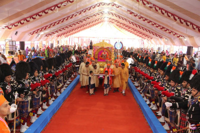 Disciples who have sponsored the scripture recitals pull the golden chariot into the grand assembly as Shree Muktajeevan Swamibapa Pipe Band perform