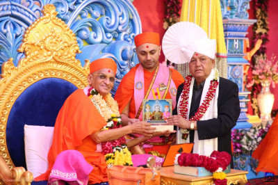 His Divine Holiness Acharya Swamishree presents the memento of the anniversary celebrations to the honoured guest