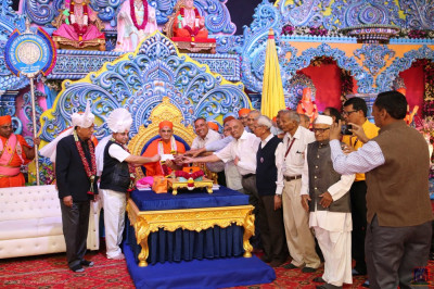 His Divine Holiness Acharya Swamishree Maharaj presents a donation to local charitable organisations