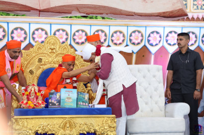 Acharya Swamishree Maharaj presents a garland of flowers to Chief Minister of Gujarat Vijay Rupani