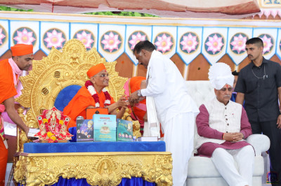 Acharya Swamishree Maharaj blesses and presents a prasad shawl and prasad to Vasanbhai Ahir - Minister of State of Gujarat