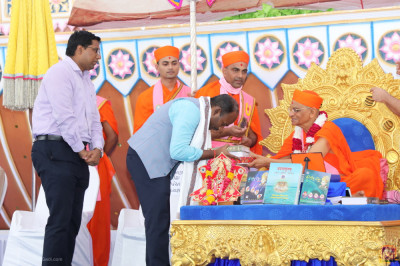 Acharya Swamishree Maharaj blesses and presents prasad to Nagrajan - Collector of Kutch