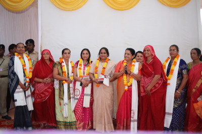 Sankhya Yogi ladies present prasad shawl, a garland of flowers and prasad to each of the honoured guests