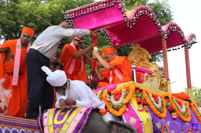 Disciples present a garland of flowers to Acharya Swamishree Maharaj