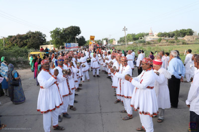 Disciples dressed in white village attire play hand cymbals and perform devotional songs during the grand procession