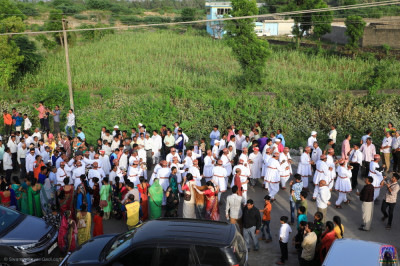 Thousands of disciples fill the streets on the outskirts of the village of Vrushpur