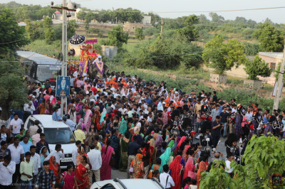 The grand procession enters the village of Vrushpur