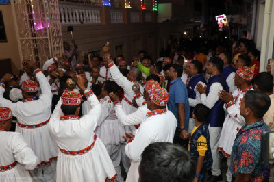 Disciples dressed in white perform devotional songs outside Shree Swaminarayan Mandir