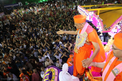 Thousands of disciples fill the grand assembly as His Divine Holiness Acharya Swamishree Maharaj dismounts from the majestic elephant
