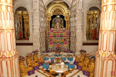 Divine darshan of Lord Shree Swaminarayan dining on a variety of chocolates and sweets